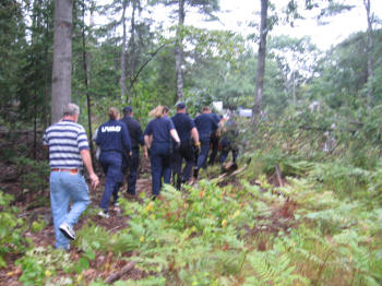 Another photo of Wardens and Orono Fire Dept. members carrying Anne Meyer out of the woods.