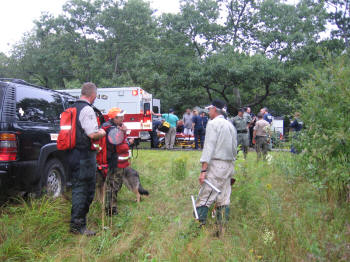 MESARD members discuss the search while Anne is put in the ambulance.